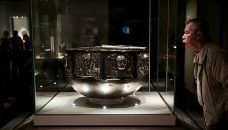 """A visitor looks at The Gundestrup cauldron displayed in the """"Celts: art and identity"""" exhibition at the British Museum in London, Britain in this September 23, 2015 file photo. REUTERS/Suzanne Plunkett/Files"""