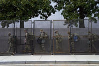 Troops walk behind security fencing on Saturday, Jan. 16, 2021, in Washington as security is increased ahead of the inauguration of President-elect Joe Biden and Vice President-elect Kamala Harris. (AP Photo/John Minchillo)