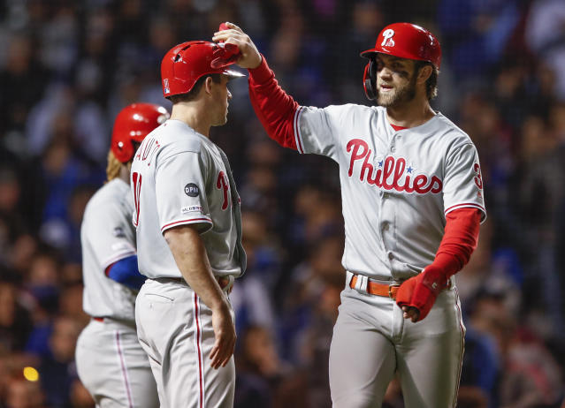 Philadelphia Phillies' Bryce Harper, right, celebrates with J.T. Realmuto, left, after scoring on a triple by Cesar Hernandez against the Chicago Cubs during the sixth inning of a baseball game, Monday, May 20, 2019, in Chicago. (AP Photo/Kamil Krzaczynski)