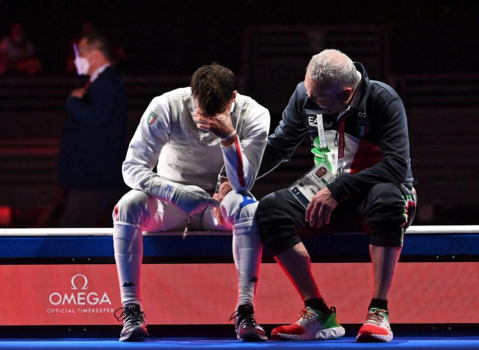 <p>Italy's Daniele Garozzo is consolate by his coach Fabio Maria Galli after loosing against Hong Kong's Cheung Ka Long on July 26 in the mens individual foil fencing gold medal match.</p>