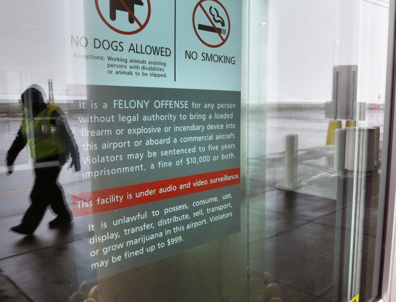 A security officer walks near a notice prohibiting marijuana possession at Denver International Airport, Monday, Jan. 27, 2014. Carrying marijuana through airport security in Colorado may get the pot confiscated, but there appears to be little danger of legal repercussions. Denver airport spokeswoman Laura Cole said the ban was enacted because Federal agencies operate at the airport and officials there did not want the inevitable conflict between state and federal laws. (AP Photo/Brennan Linsley)