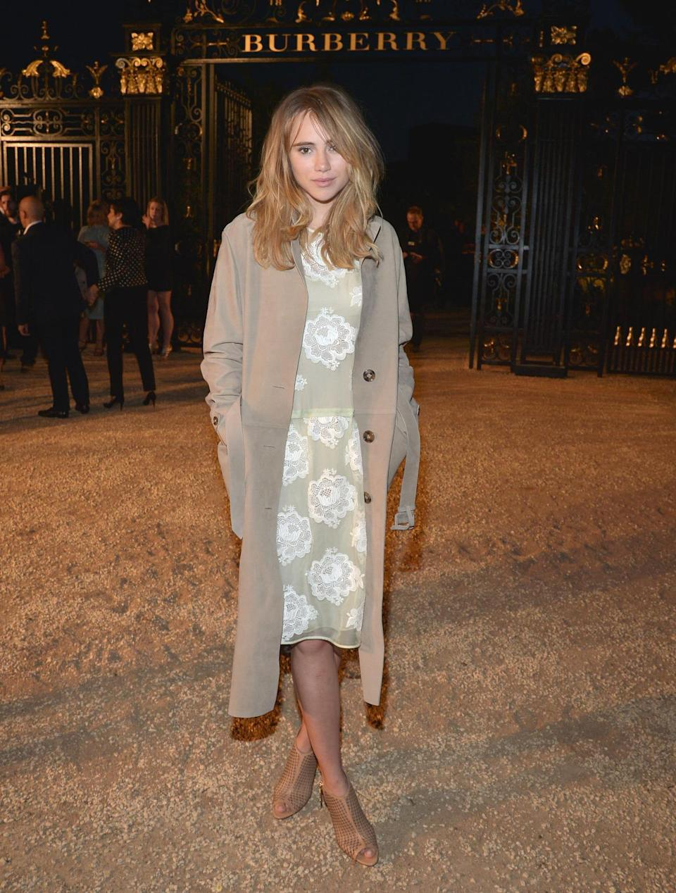 Suki Waterhouse in a floral beige dress with white flowers and khaki-colored coat represented Burberry in a classic, yet fresh, manner.