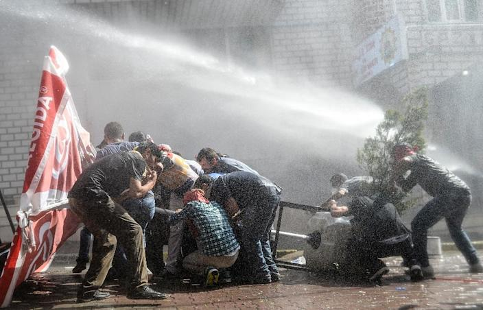 Protesters protect themselves as Turkish riot police fire water cannons to disperse a demonstration in Istanbul's Gazi district, on July 26, 2015 (AFP Photo/Bulent Kilic)