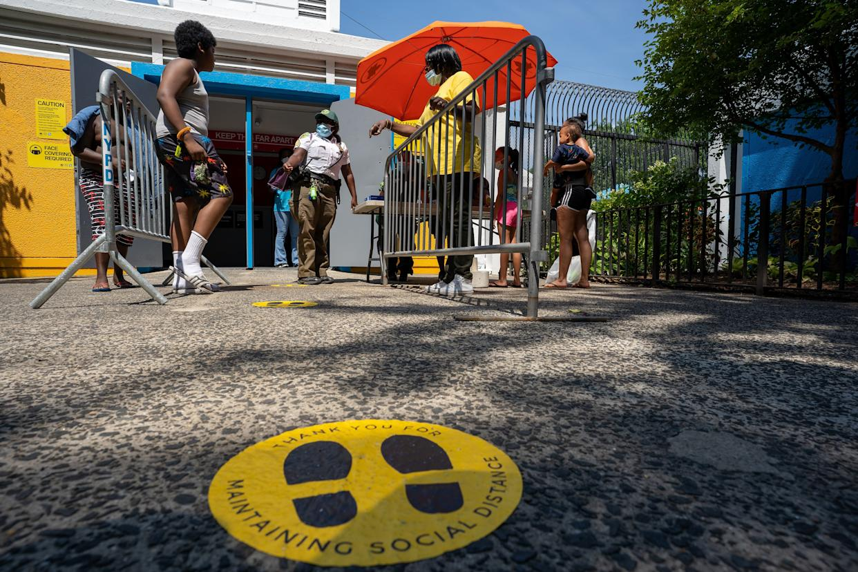 People enter the pool at Mullaly Park on the second day of opening following the phase four guideline in response to the COVID-19 pandemic on July 25, 2020, in the Bronx borough of New York City. A wrist band and queue system are in place if the pool is at capacity.