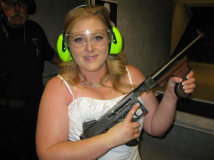 """This July 28, 2012 photo provided by Bob MacDuff shows Lindsae MacDuff holding an automatic weapon at the Gun store in Las Vegas after her """"shotgun wedding."""" One Las Vegas shooting range is selling """"take a shot at love"""" packages that include 50 submachine gun rounds. Another is offering wedding packages in which the bride and groom can pose with Uzis and ammunition belts. And a third invites lovebirds to renew their vows and shoot a paper cutout zombie in the face. (AP Photo/Bob MacDuff)"""
