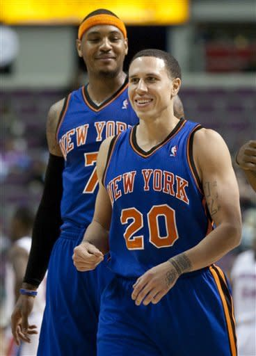 New York Knicks' Mike Bibby (20) smiles as he walks off the court with Carmelo Anthony (7) after hitting a three-point shot against the Detroit Pistons in an NBA basketball game Saturday, Jan. 7, 2012, in Auburn Hills, Mich. Bibby scored 16 points in the Knicks 103-80 win. (AP Photo/Duane Burleson)
