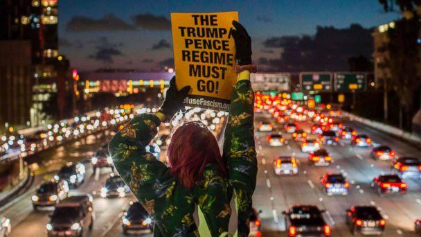 PHOTO: Protestors shout slogans and hold signs during the State of the Union protest on a freeway overpass in downtown Los Angeles, Feb. 05, 2019. (Apu Gomes/AFP/Getty Images)