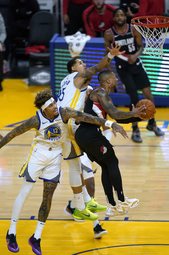 Portland Trail Blazers guard Damian Lillard (0) drives to the basket against Golden State Warriors' Kelly Oubre Jr. (12) and Juan Toscano-Anderson, center, during the first half of an NBA basketball game in San Francisco, Friday, Jan. 1, 2021. (AP Photo/Tony Avelar)