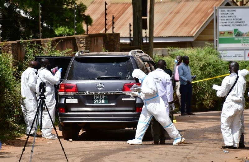 Forensic experts secure the scene of an attempted assassination on Ugandan minister of works and transport General Katumba Wamala, in the suburb of Kiasasi within Kampala