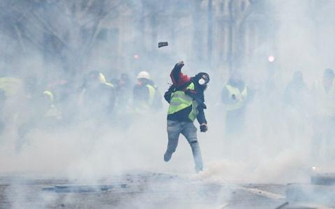 """A protestor wearing a """"yellow vest"""" (Gilet jaune) throws a cobble at police forces - Credit: THOMAS SAMSON/AFP/Getty Images"""