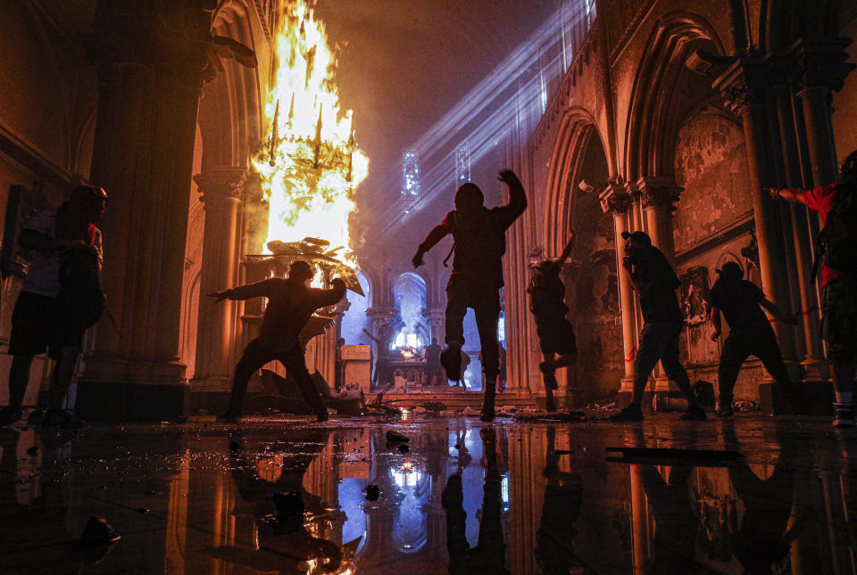Protesters storm the San Francisco de Borja church, which belongs to the Carabineros, Chile's national police force, in Santiago, Chile, on Oct. 18, 2020, the first anniversary of the start of anti-government mass protests over inequality. (AP Photo/Esteban Felix)