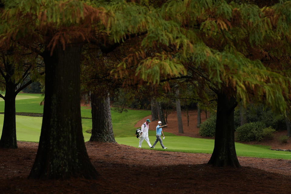 Sung Kang, of South Korea, walks with his caddie along the 13th fairway during a practice round for the Masters golf tournament Wednesday, Nov. 11, 2020, in Augusta, Ga. (AP Photo/Charlie Riedel)