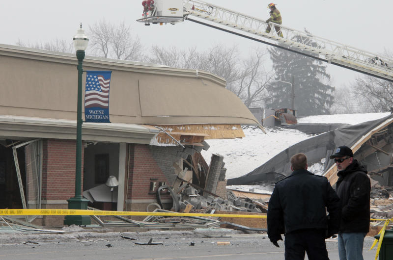 A firefighter on a ladder surveys the damage after an apparent gas explosion at William C. Franks Furniture store on Wednesday, Dec. 29, 2010 in Wayne, Mich. Wayne City Manager John Zech says owner Paul Franks is in critical condition in the burn unit of the University of Michigan Hospital in Ann Arbor.   (AP Photo/Jerry S. Mendoza)