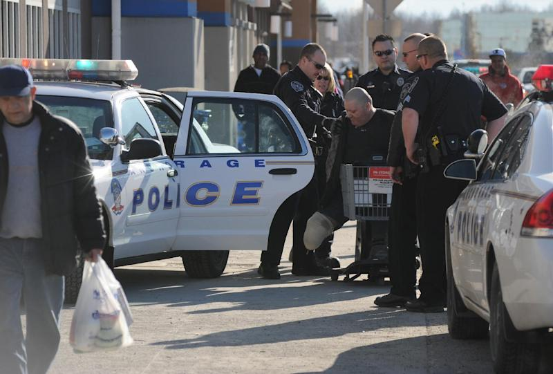 Anchorage police officers place Daniel Pirtle into custody after a shooting at the midtown Walmart on Saturday, March 16, 2013 in Anchorage, Alaska.  Pirtle, 45, has been charged with assault and misconduct involving a weapon.  Anchorage Police Department spokeswoman Anita Shell says Pirtle, who is a double-amputee, is accused of shooting 33-year-old Jason Mahi. Police say Pirtle shot Mahi on Saturday in the abdomen after the manager asked him to put his service dog on a leash. Shell said an off-duty police officer who was shopping at the time detained the suspect as he was trying to leave the store in his motorized cart.   (AP Photo/Anchorage Daily News, Bob Hallinen)  MANDATORY CREDIT TO THE ANCHORAGE DAILY NEWS/BOB HALLINEN