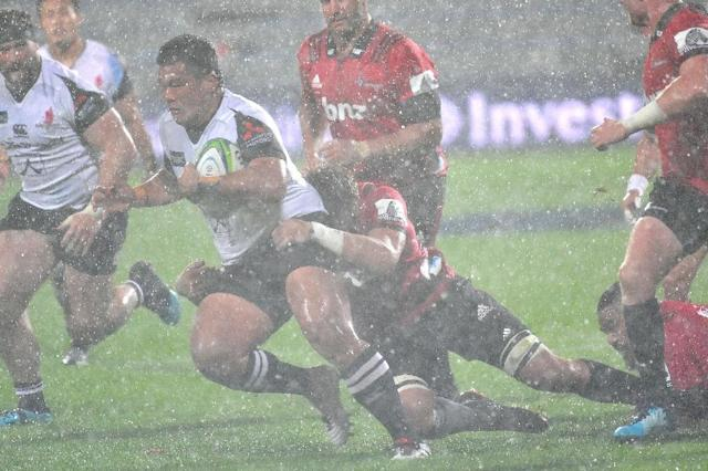 Sunwolves' Koo Ji-woo is tackled by Crusaders' Ethan Blackadder as a massive hailstorm rages in Christchurch (AFP Photo/Marty MELVILLE)
