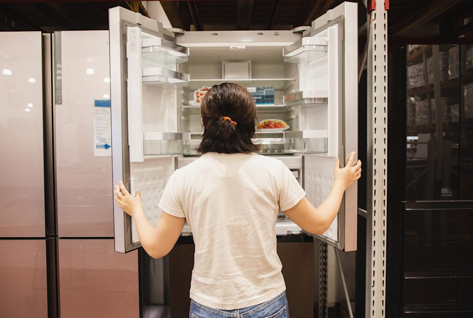 Asian woman shopping for refrigerator