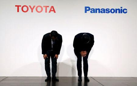 Toyota Motor Corp President Akio Toyoda (L) and Panasonic Corp President Kazuhiro Tsuga bow as they attend a photo session after a joint news conference in Tokyo, Japan, December 13, 2017.  REUTERS/Toru Hanai