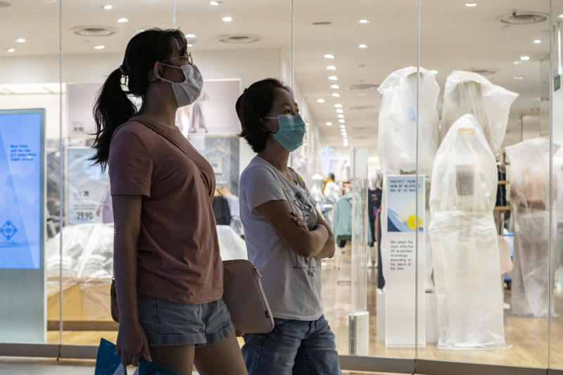 SINGAPORE, SINGAPORE - APRIL 6: People wearing protective face masks walk past a closed retail store in a shopping mall on April 6, 2020 in Singapore, a day before a 'circuit breaker' takes effect. The Singapore government will close all schools and most workplaces and limit social interactions and movement outside homes for at least a month to stem the spike in local coronavirus cases.(Photo by Ore Huiying/Getty Images)