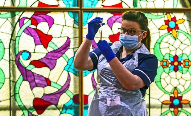Practice nurse Hannah Currie, 25, prepares a dose of the AstraZeneca vaccine at Bradford Central Mosque (Peter Byrne/PA)