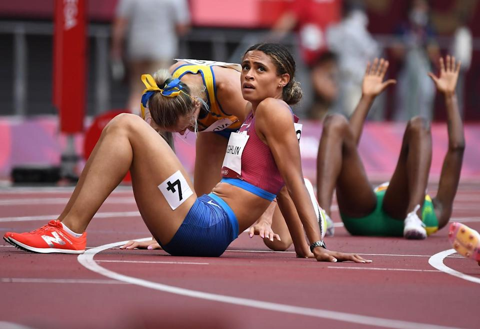 Sydney McLaughlin and other runners rest on the track after racing at the Tokyo Olympics.