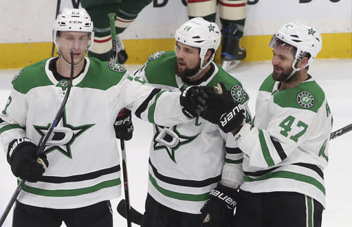 Dallas Stars' Alexander Radulov, right, of Russia, is congratulated by Esa Lindell, left, of Finland, and Jamie Benn after scoring an empty-net goal against the Minnesota Wild in the third period of an NHL hockey game Thursday, March 14, 2019, in St. Paul, Minn. (AP Photo/Jim Mone)