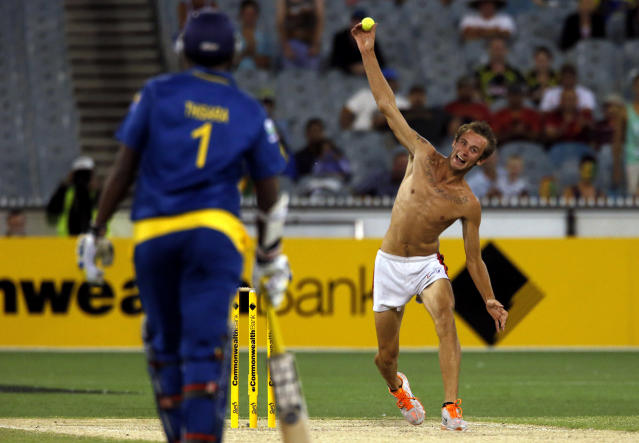A member of the crowd, who ran onto the pitch, bowls a tennis ball on the pitch as Sri Lanka's Thisara Perera looks on during the one-day international cricket match between Australia and Sri Lanka at the Melbourne Cricket Ground January 11, 2013. REUTERS/David Gray (AUSTRALIA - Tags: SPORT CRICKET TPX IMAGES OF THE DAY)
