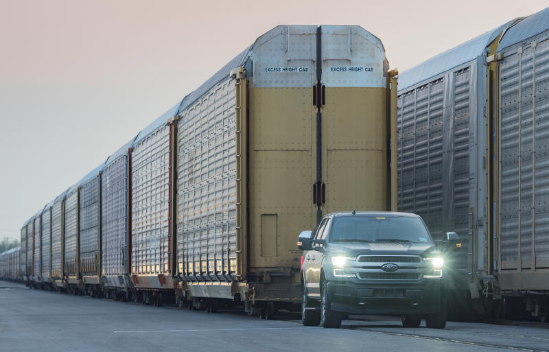 A prototype electric F-150 pickup, which looks like a standard 2019 model, is shown preparing to pull a line of double-decker rail cars.