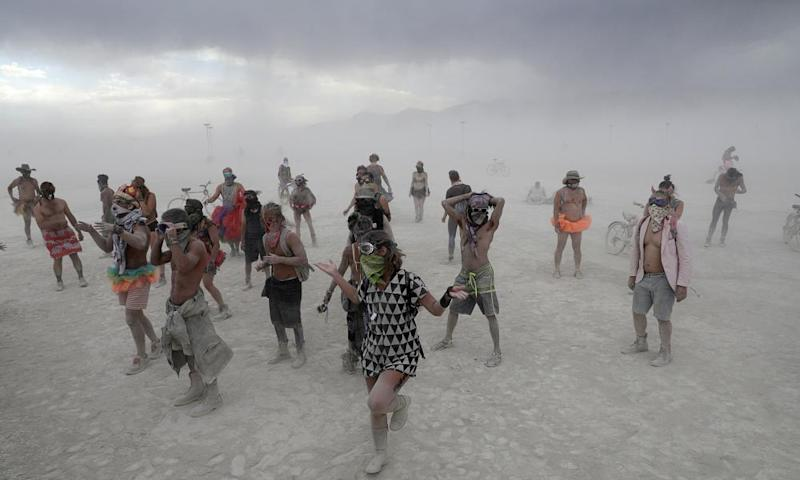 Burning Man participants dance to the music of an art car in a driving desert dust storm in 2017.