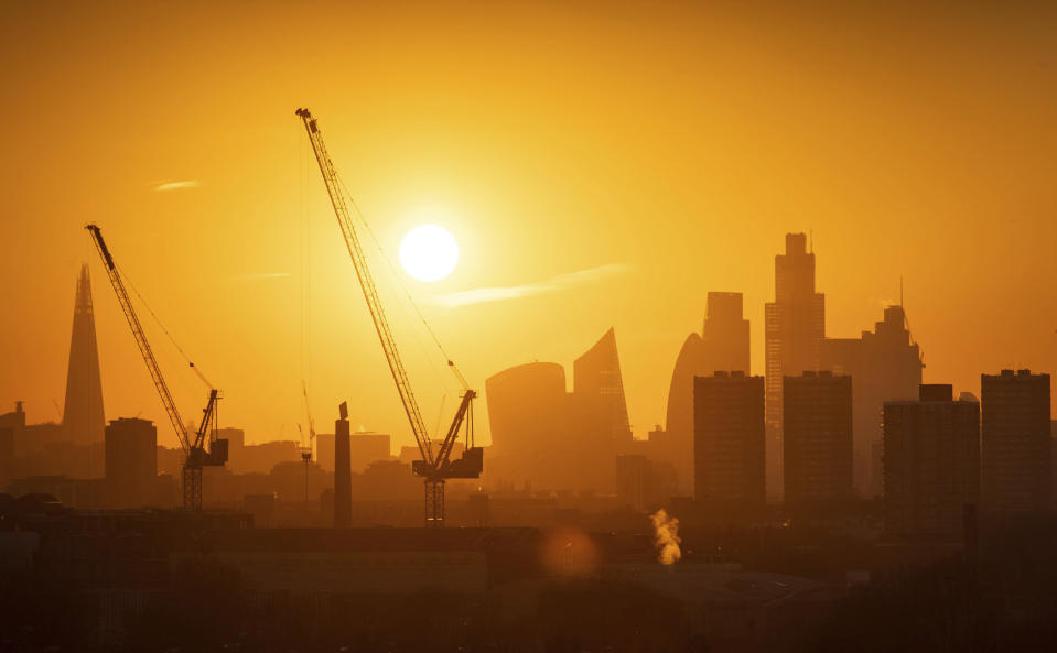 The sun sets behind tower cranes and the London skyline, including the Shard building at left, and other skyscrapers in the city financial district of London, Tuesday Jan. 21, 2020. (Dominic Lipinski/PA via AP)