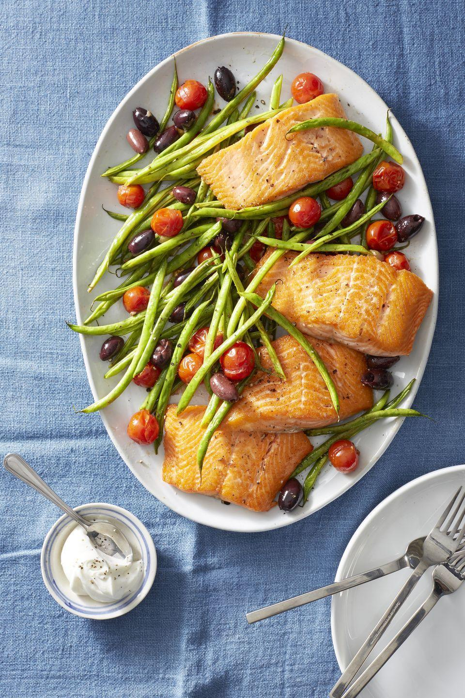 """<p>Believe it or not, there are two fishes hiding in this sea of spring veggies: Salmon <em>and</em> anchovies. This 300-calorie dinner is ready in just 20 minutes. <br></p><p><a href=""""https://www.goodhousekeeping.com/food-recipes/easy/a22749664/roasted-salmon-with-green-beans-and-tomatoes-recipe/"""" rel=""""nofollow noopener"""" target=""""_blank"""" data-ylk=""""slk:Get the recipe for Roasted Salmon With Green Beans and Tomatoes »"""" class=""""link rapid-noclick-resp""""><em>Get the recipe for Roasted Salmon With Green Beans and Tomatoes »</em></a></p>"""
