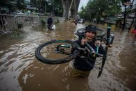 Man carries his bicycle through water in an area affected by floods following heavy rains in Jakarta