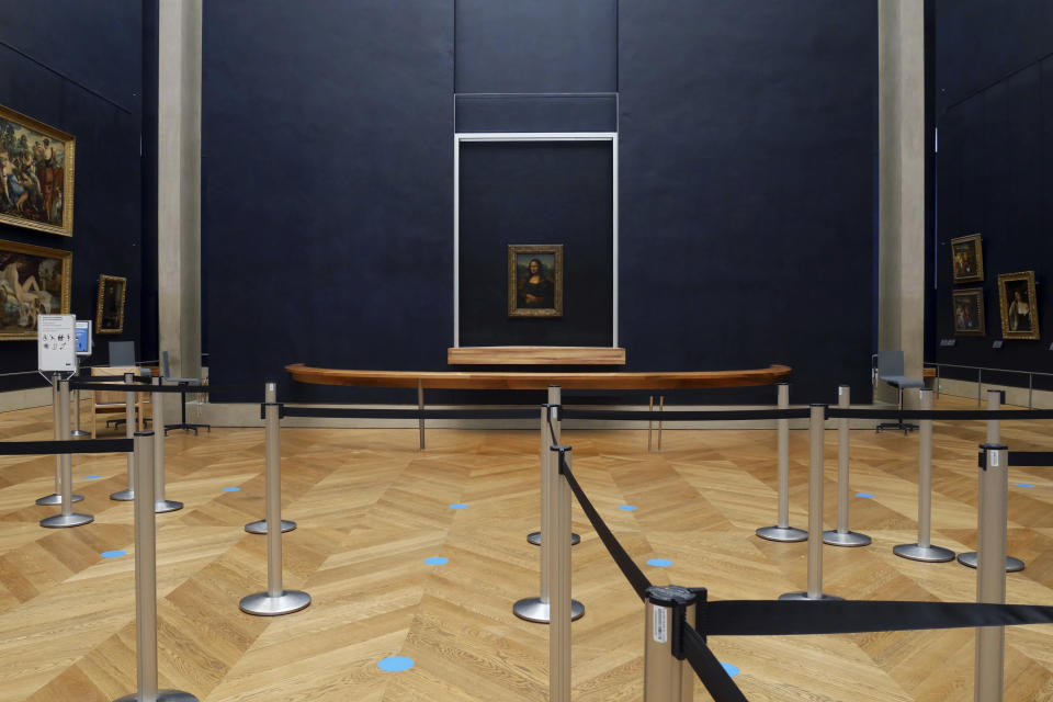Leonardo da Vinci's Mona Lisa hangs on the wall in a deserted Louvre museum, in Paris, Thursday, Feb. 11, 2021. The 518-year-old Mona Lisa will have seen many things in her life on display, but rarely this: Almost four months with no visitors. She stares out in Paris' Louvre, across bulletproof glass into the now-silent emptiness of the shuttered Salle des Etats. (AP Photo/Thibault Camus)