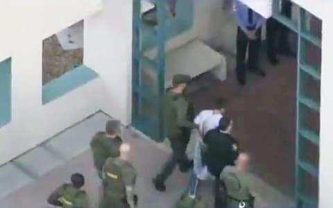Police escort a suspect into the Broward Jail after checking him at the hospital following a shooting incident at Marjory Stoneman Douglas High School in Parkland - Credit: Reuters