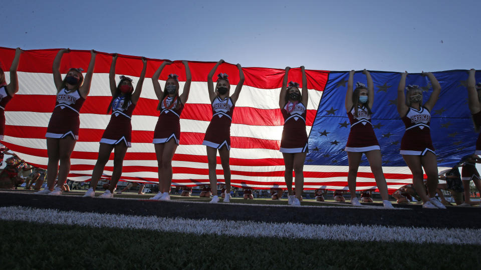 Herriman cheerleaders raise the American flag before the start of a high school football game between Davis and Herriman on Thursday, Aug. 13, 2020, in Herriman, Utah. Utah is among the states going forward with high school football this fall despite concerns about the ongoing COVID-19 pandemic that led other states and many college football conferences to postpone games in hopes of instead playing in the spring. (AP Photo/Rick Bowmer)