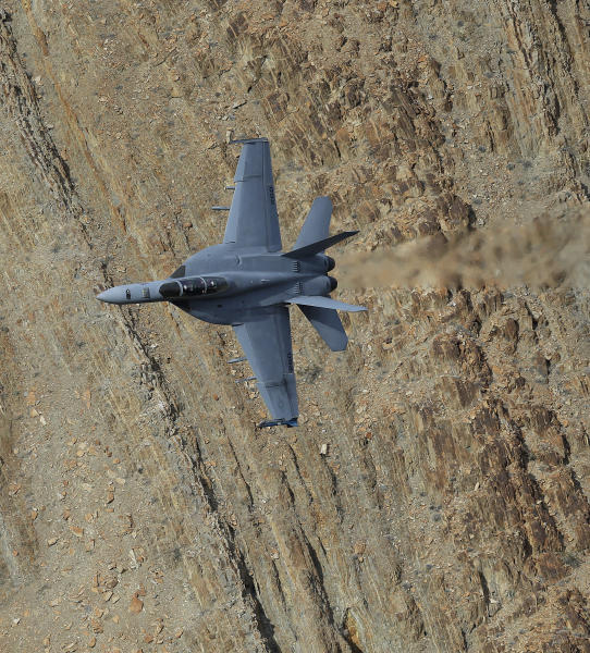 In this Feb. 27, 2017, photo, an F/A-18F Super Hornet from China Lake VX-9 Vampire squadron flies through the nicknamed Star Wars Canyon in Death Valley National Park, Calif. Military jets roaring over national parks have long drawn complaints from hikers and campers. But in California's Death Valley, the low-flying combat aircraft skillfully zipping between the craggy landscape has become a popular attraction in the 3.3 million acre park in the Mojave Desert, 260 miles east of Los Angeles. (AP Photo/Ben Margot)