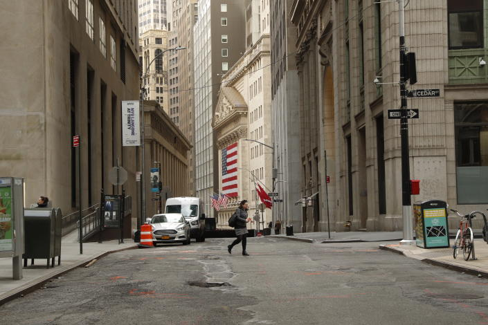 A woman walks on a nearly empty street near the New York Stock Exchange (NYSE) in New York, U.S., March 18, 2020. REUTERS/Lucas Jackson