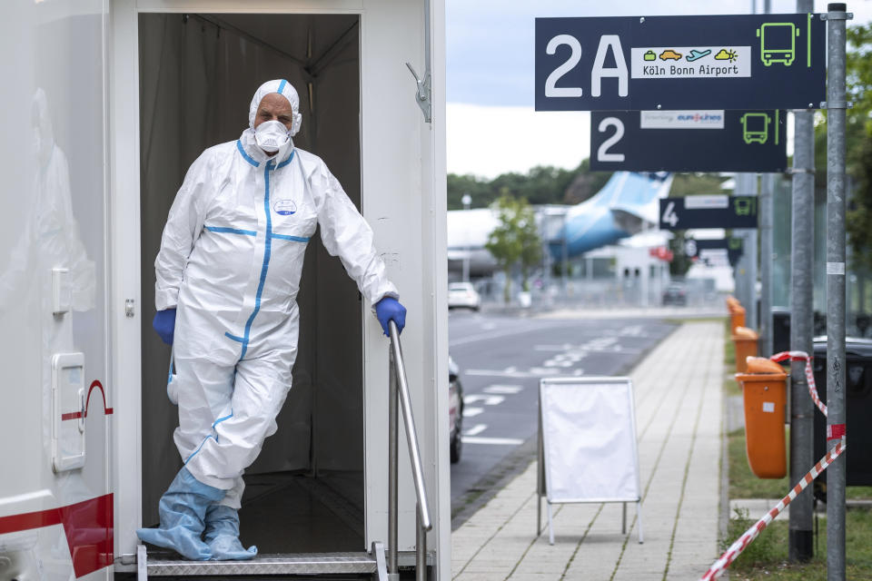 A person in protective clothes stand in the entrance of test station for the coronavirus at Cologne/Bonn Airport in Cologne, Germany, Saturday, July 25, 2020. Free corona tests for returnees from countries designated as risk areas have begun at the German airports in Düsseldorf, Cologne / Bonn and Dortmund. (Marius Becker/dpa via AP)