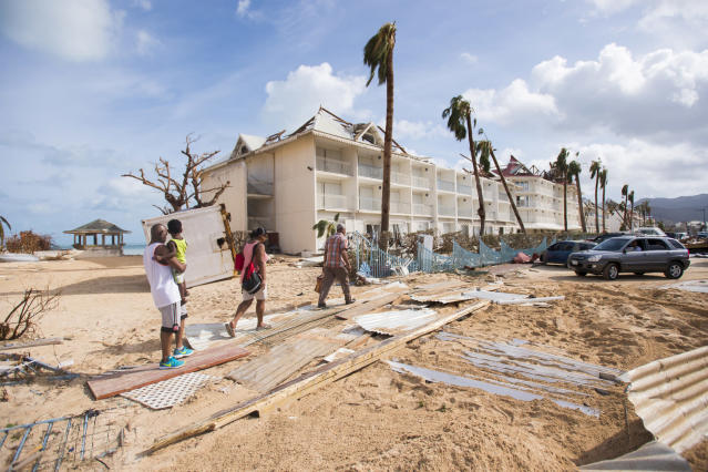 <p>People walk through damage on Sept. 7, 2017, in a sand-covered street of Marigot, near the Bay of Nettle, on the island of Saint-Martin in the northeast Caribbean, after the passage of Hurricane Irma. (Photo: Lionel Chamoiseau/AFP/Getty Images) </p>