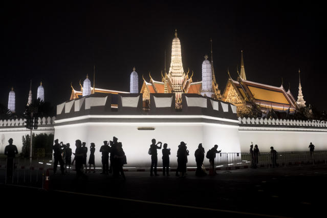 <p>Mourners take photographs outside Wat Phra Kaew, or he Temple of the Emerald Buddha on Oct. 27, 2017 in Bangkok, Thailand. (Photo: Brent Lewin/Getty Images) </p>