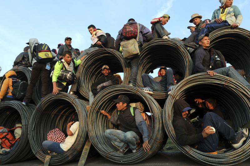 Central American migrants, part of the caravan hoping to reach the U.S. border, get a ride on a truck carrying rolls of steel rebar, in Irapuato, Mexico, Monday, Nov. 12, 2018. Several thousand Central American migrants marked a month on the road Monday as they hitched rides to the western Mexico city of Guadalajara and toward the U.S. border. (AP Photo/Rodrigo Abd)