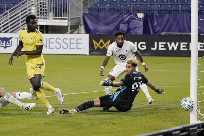 A shot by Nashville midfielder Derrick Jones (21) goes wide of the goal as Minnesota United goalkeeper Dayne St. Clair (97) looks back at the ball during the first half of an MLS soccer match Tuesday, Oct. 6, 2020, in Nashville, Tenn. (AP Photo/Mark Humphrey)