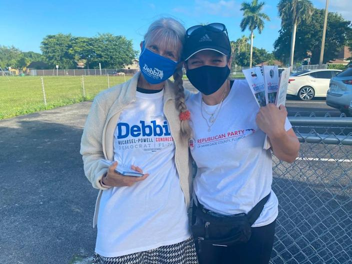 Anne Smith, a Democratic volunteer (left) and Marissa Gutierrez, a Republican volunteer (right) hug it out at Calusa Elementary School in West Kendall, one of the community's Election Day precincts on Nov. 3, 2020.