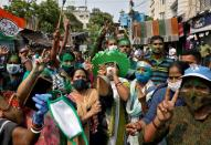 Supporters of Chief Minister of West Bengal state and the Chief of Trinamool Congress (TMC) Mamata Banerjee celebrate after the initial poll results, in Kolkata