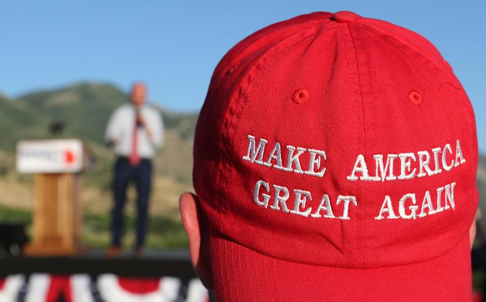 """A Romney supporter listens to a speaker as he wears a """"Make America Great Again"""" hat at a Mitt Romney election party in Orem, Utah, June 26, 2018. (Photo: George Frey/Getty Images)"""