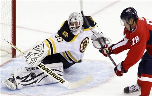 Boston Bruins goalie Tim Thomas (30) deflects a shot by Washington Capitals left wing Alexander Semin (28), of Russia, during the first period of an NHL hockey game in Washington, Sunday, Feb. 5, 2012. (AP Photo/Ann Heisenfelt)