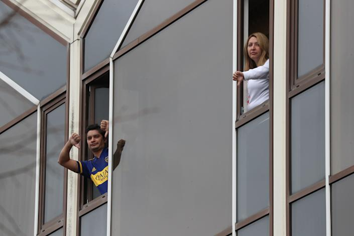 Two quarantined travellers in the same room making a thumbs down gesture out of their windows in the Radisson Blu Edwardian hotel, near Heathrow Airport, London, a Government-designated quarantine hotel being used for travellers to stay during a 10-day quarantine after returning to England from one of 33