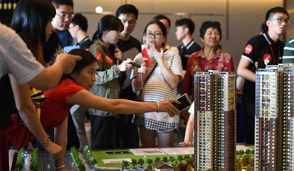 Potential buyers crowd around a model of a residential compound by China Vanke in Dongguan, Guangdong province. Photo: Reuters