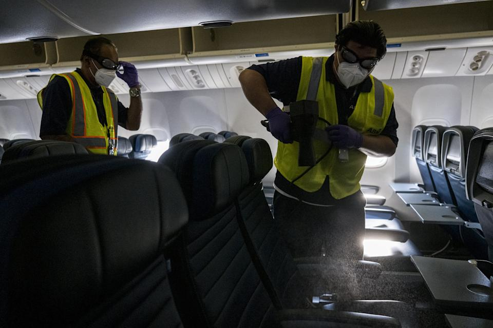 Workers use an electrostatic cleaning sprayer inside an airplane