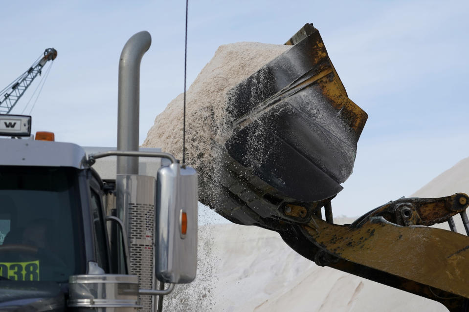 A front-end loader at Eastern Salt Company pours road salt into a dump truck to deliver to area municipal depots, Wednesday, Dec. 16, 2020, in Chelsea, Mass., as preparation continues for a storm that is expected to dump a foot or more of snow throughout the Northeast. (AP Photo/Elise Amendola)