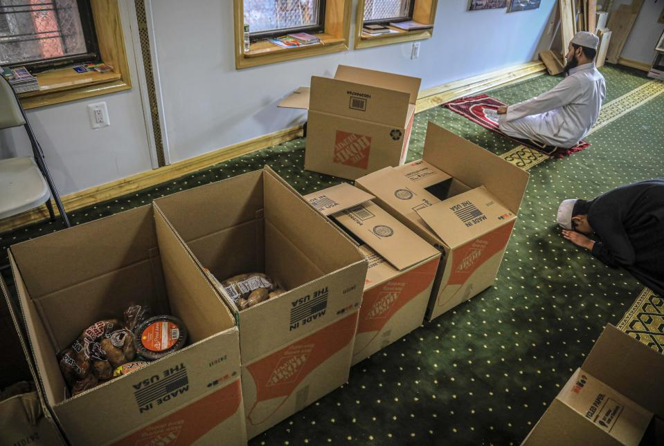 In this Wednesday, April 22, 2020, photo, Imam Mufti Mohammed Ismail, leader of An-Noor Cultural Center and masjid that serves a mostly Bangladeshi Muslim community in the Elmhurst neighborhood in the Queens borough of New York, and his son Hassan, 13, right, pray near boxes of food supplies being prepared for distribution to those impacted by COVID-19 restrictions. Ismaill says this gives the center the opportunity to fulfill one of Ramadan's tenets — to serve those less fortunate, regardless of religion. (AP Photo/Bebeto Matthews)